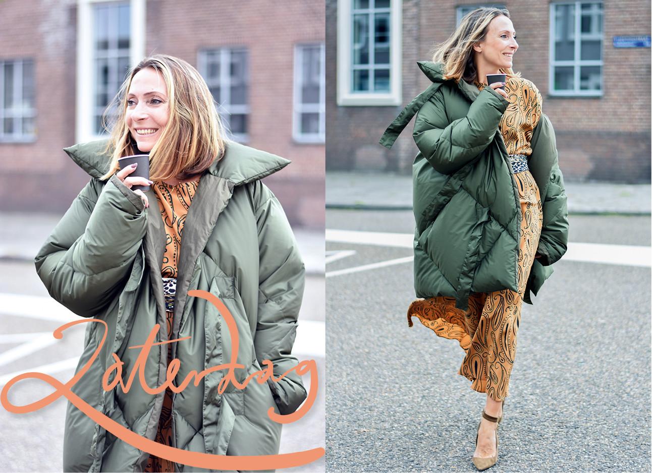 May die een donker groene jas draagt met daaronder een oranje jurk, ze loopt midden op straat