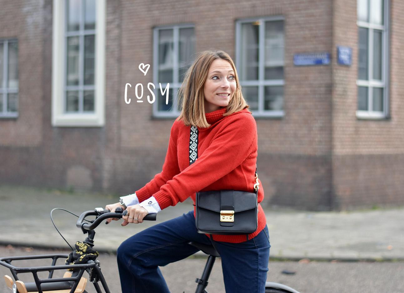 may die in een rode trui op een zwarte fiets buiten staat