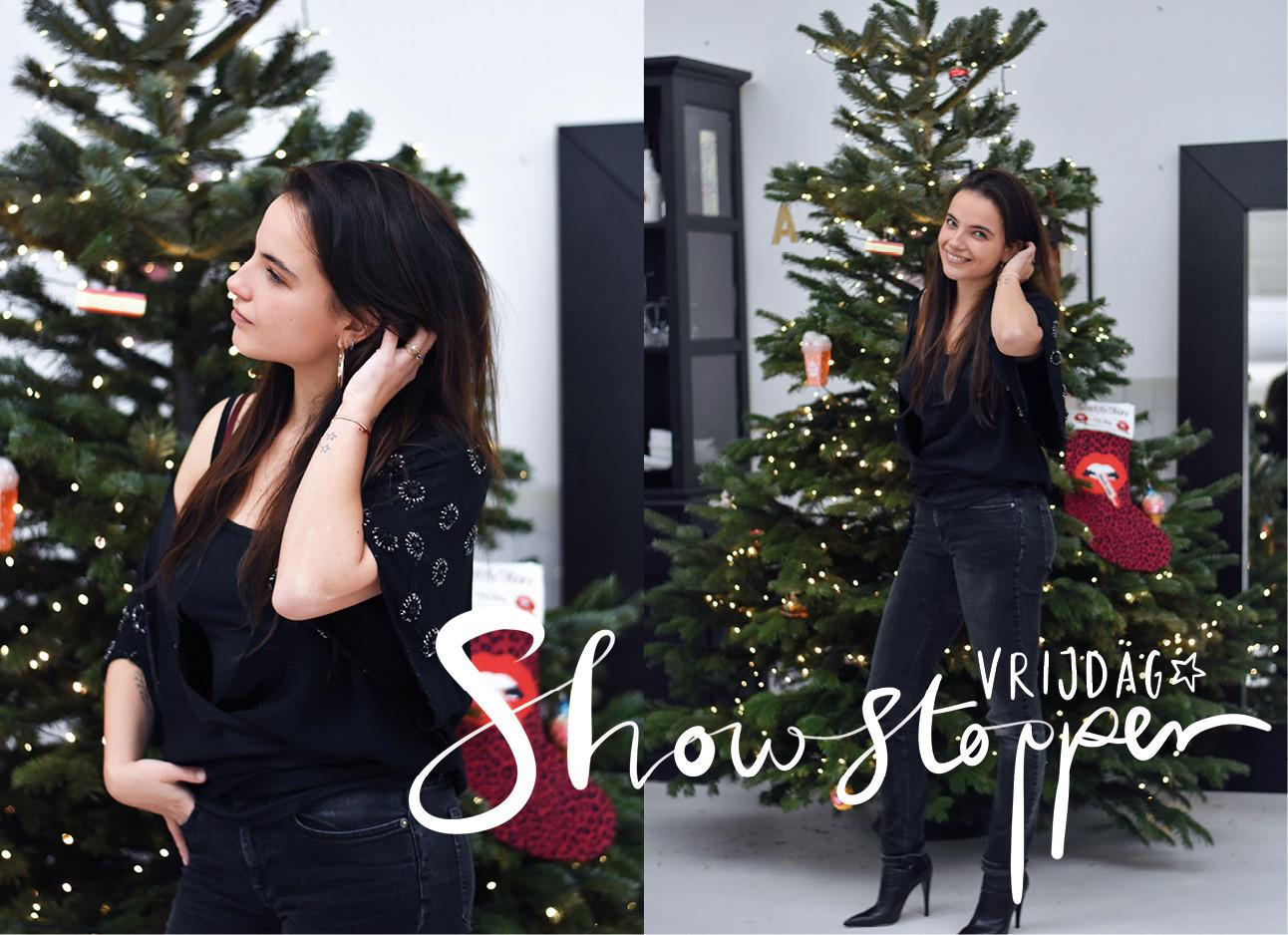 tess hoens die in een zwarte outfit voor een groene kerstboom staat