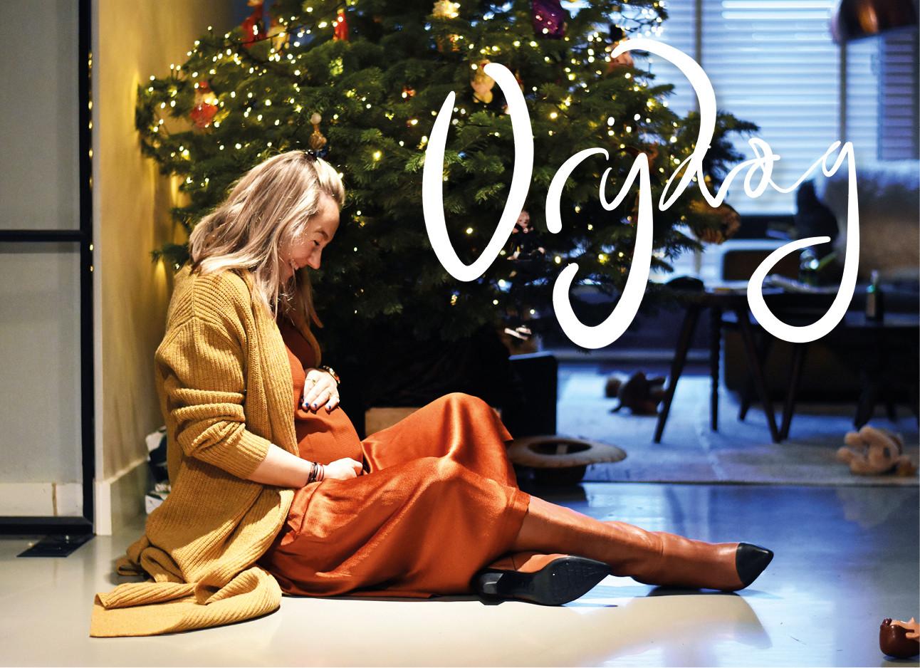 beeld van carolien in een oranje jurk bij de kerstboom