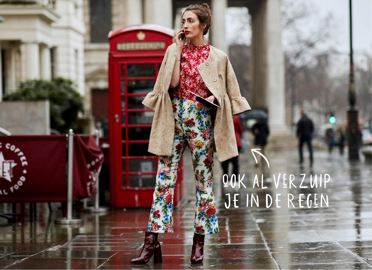 vrouw in london met rode telefooncel in de regen