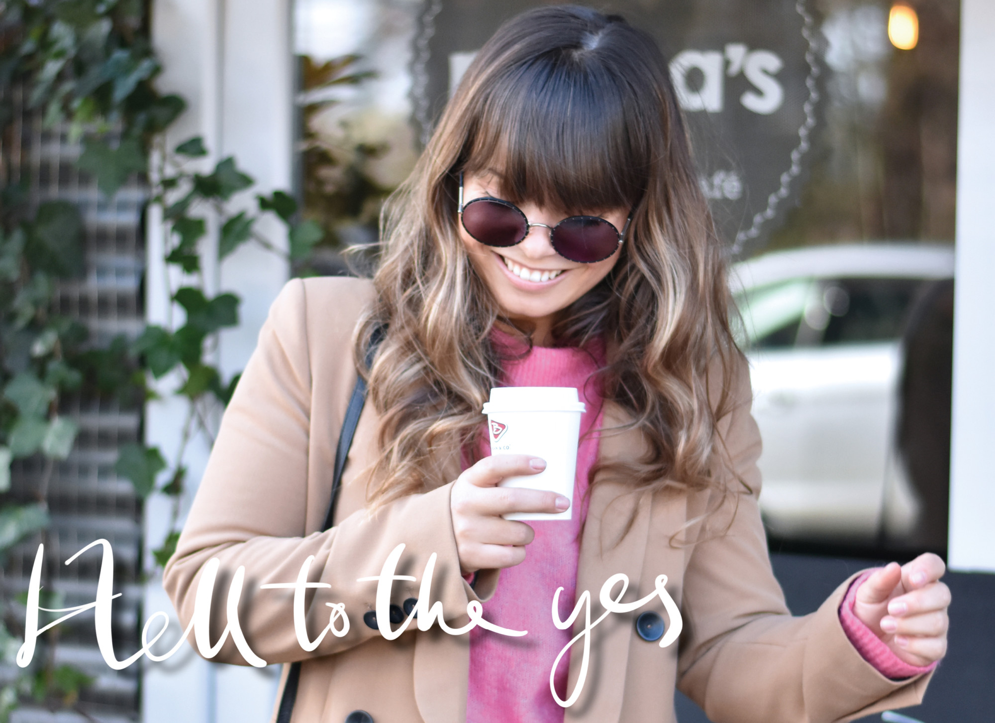kiki met cognac jas en roze trui met zonnebril en koffie in haar hand voor een plant