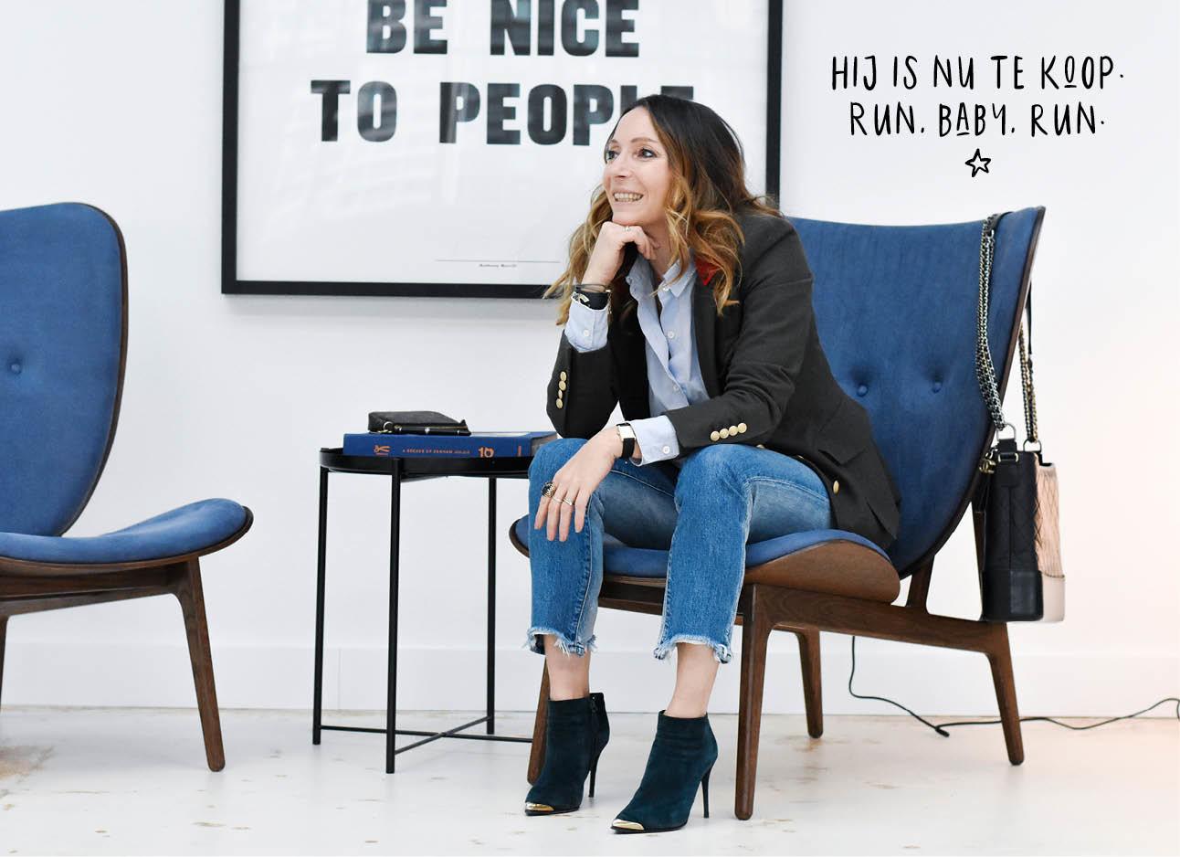 May-britt zittend in een blauwe stoel in het hoofdkantoor van Denham lachend