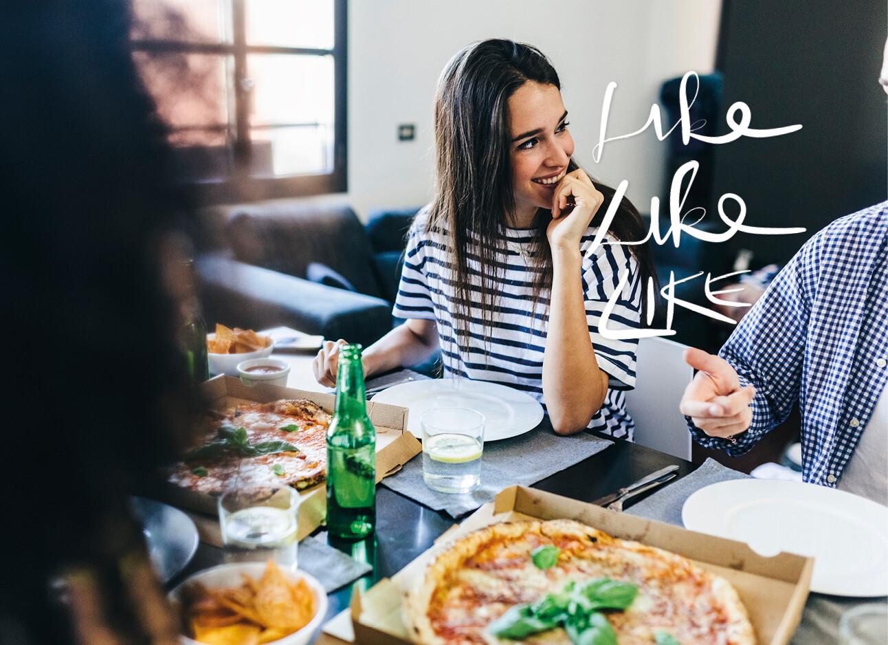 vrouw pizza eten kijkt verliefd naar een man