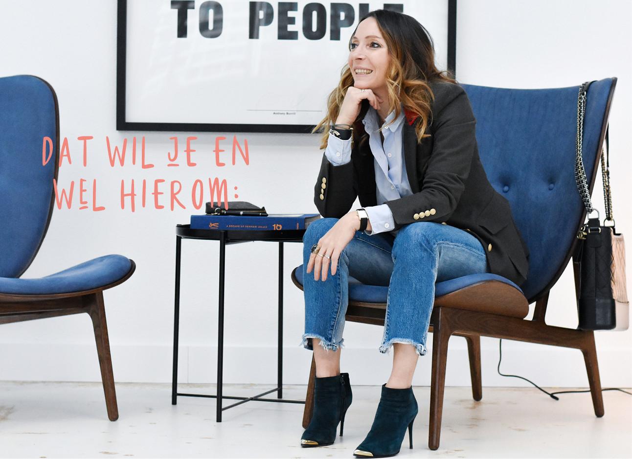maybritt mobach zit op een donkerblauwe stoel, ze draagt jeans, blauwe blouse en een colbert, aan de stoel hangt een tas boeken op tafel
