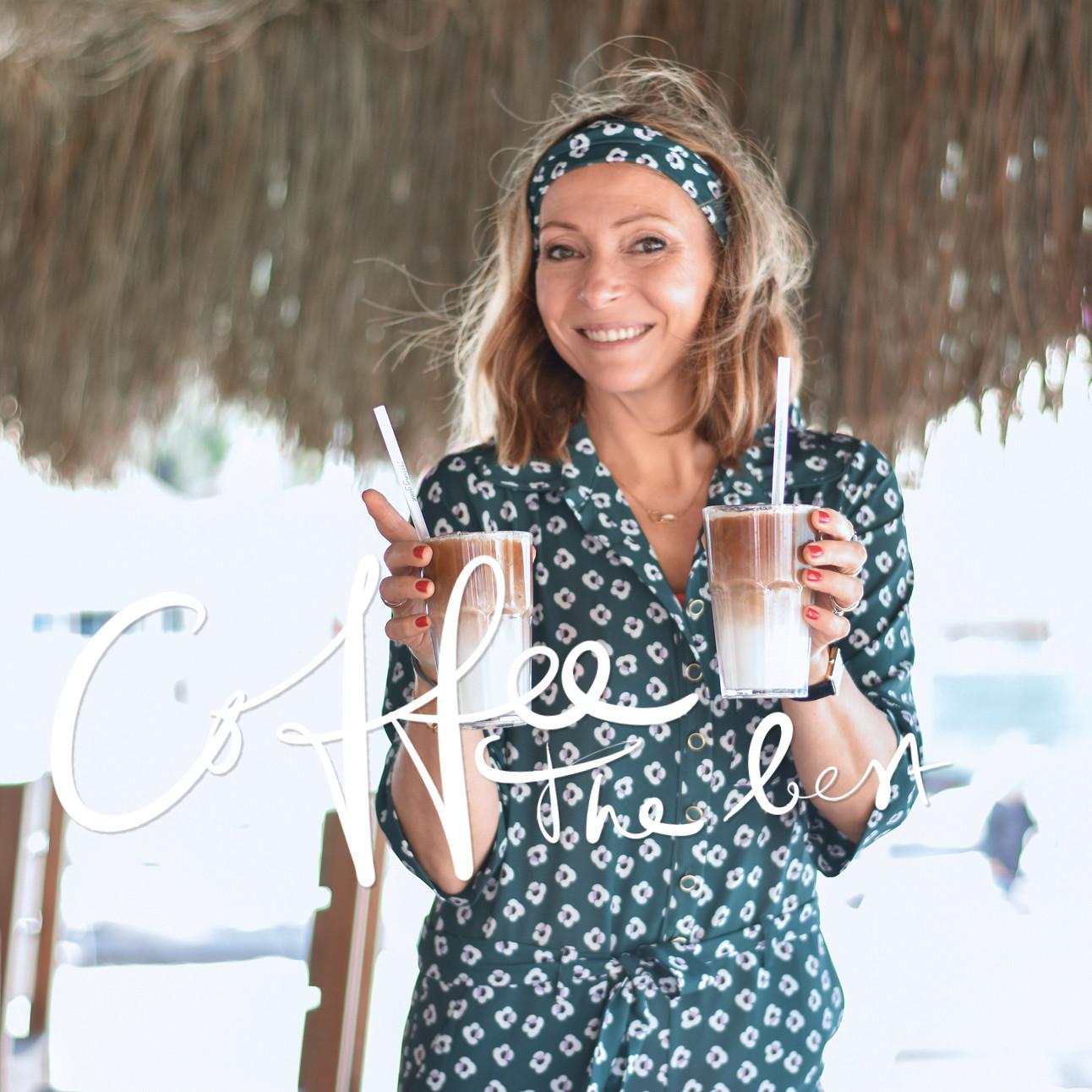 may lachend op het strand met twee ijs koffies in haar handen