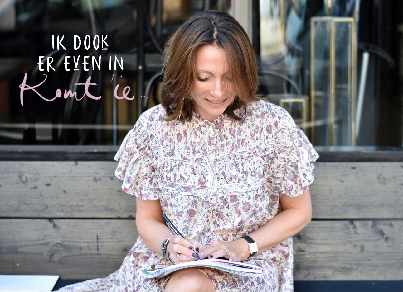 May zittend op een bankje in bloemige jurk kijkend naar een schrift