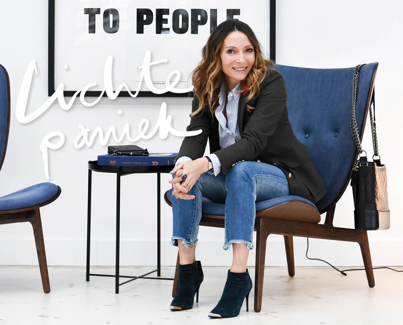 May-britt lachend op een blauwe stoel hoofdkantoor Denham in Amsterdam jeans met hoge hakken lachend