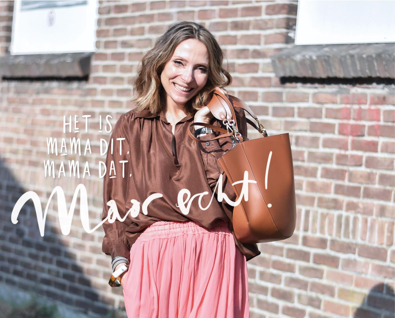 May-britt lachend met een bruine zijde top en een roze rok Wandler tas