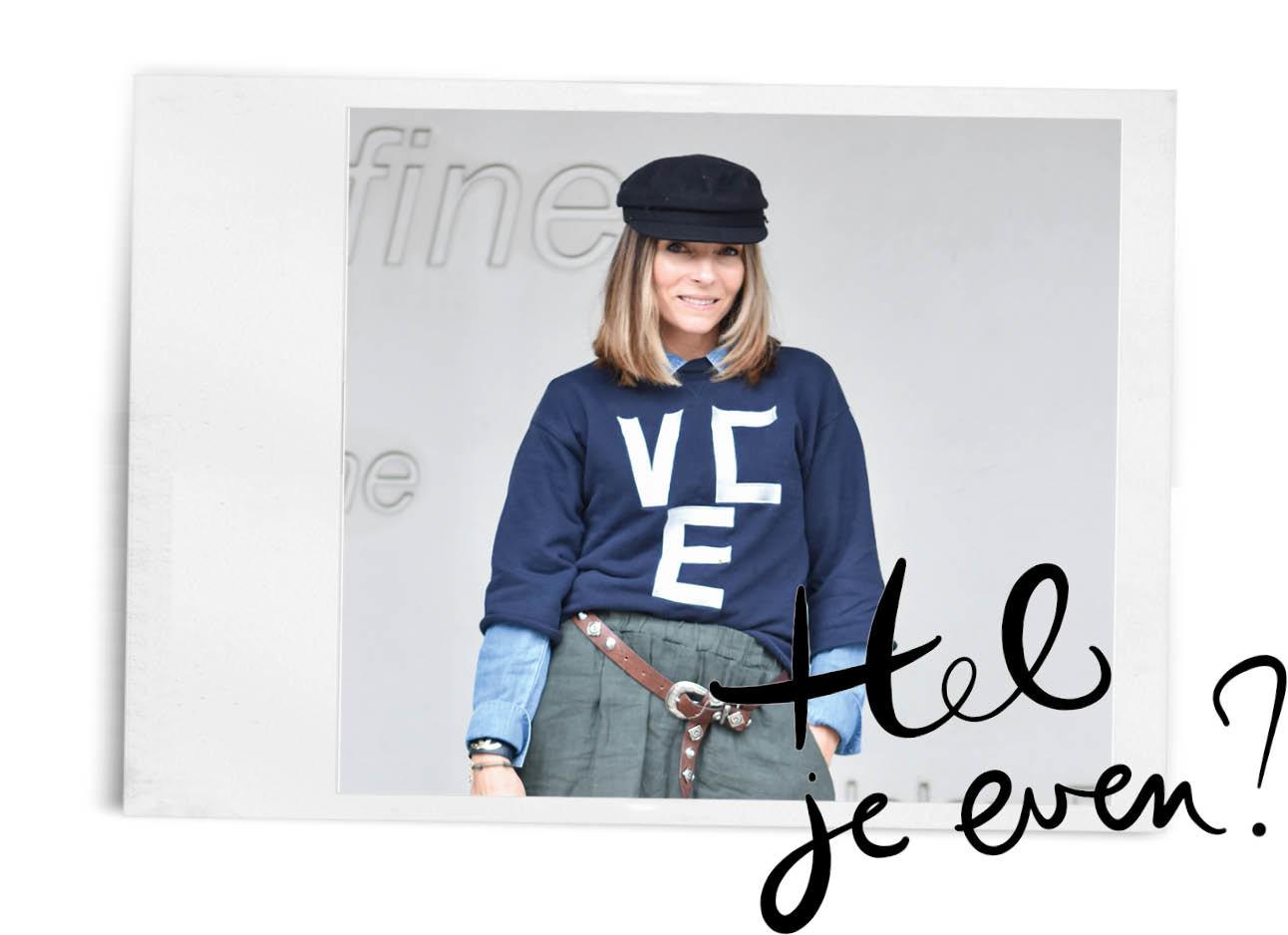 may-lachend met een blauw hoedje op en grote trui met witte letters