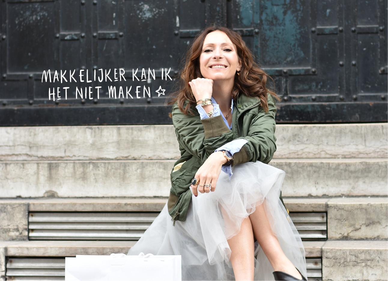 may-britt lachend op een trap in parijs met een tulle rok aan en een groen bomberjack