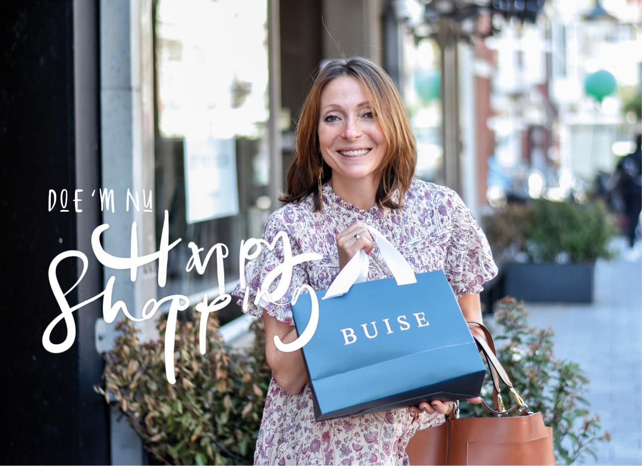 may lachend op straat met een shopping tasje van Buise in Amsterdam
