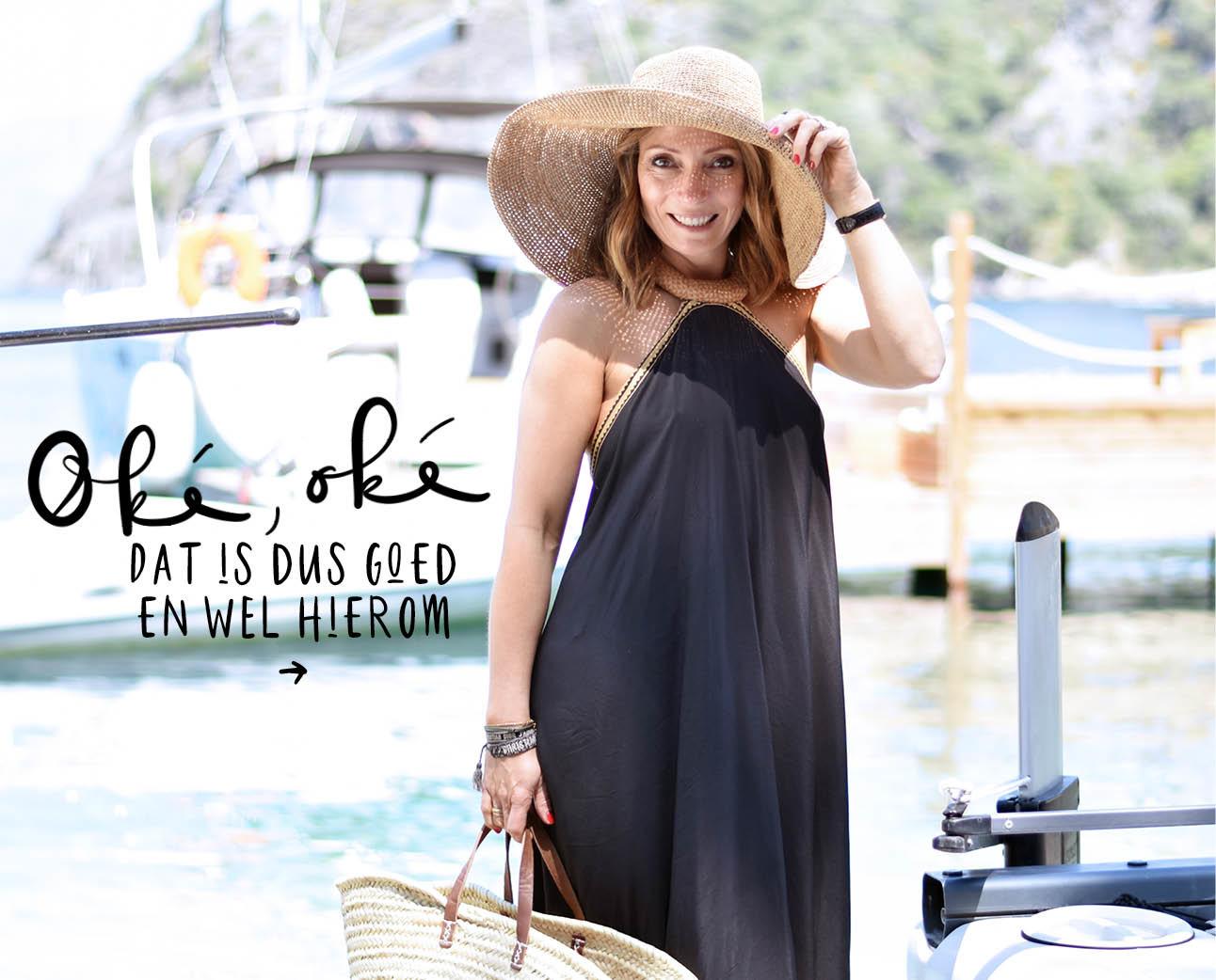 May-britt lachend op het strand bij het water met grote rieten hoed om en donker blauwe lange jurk aan