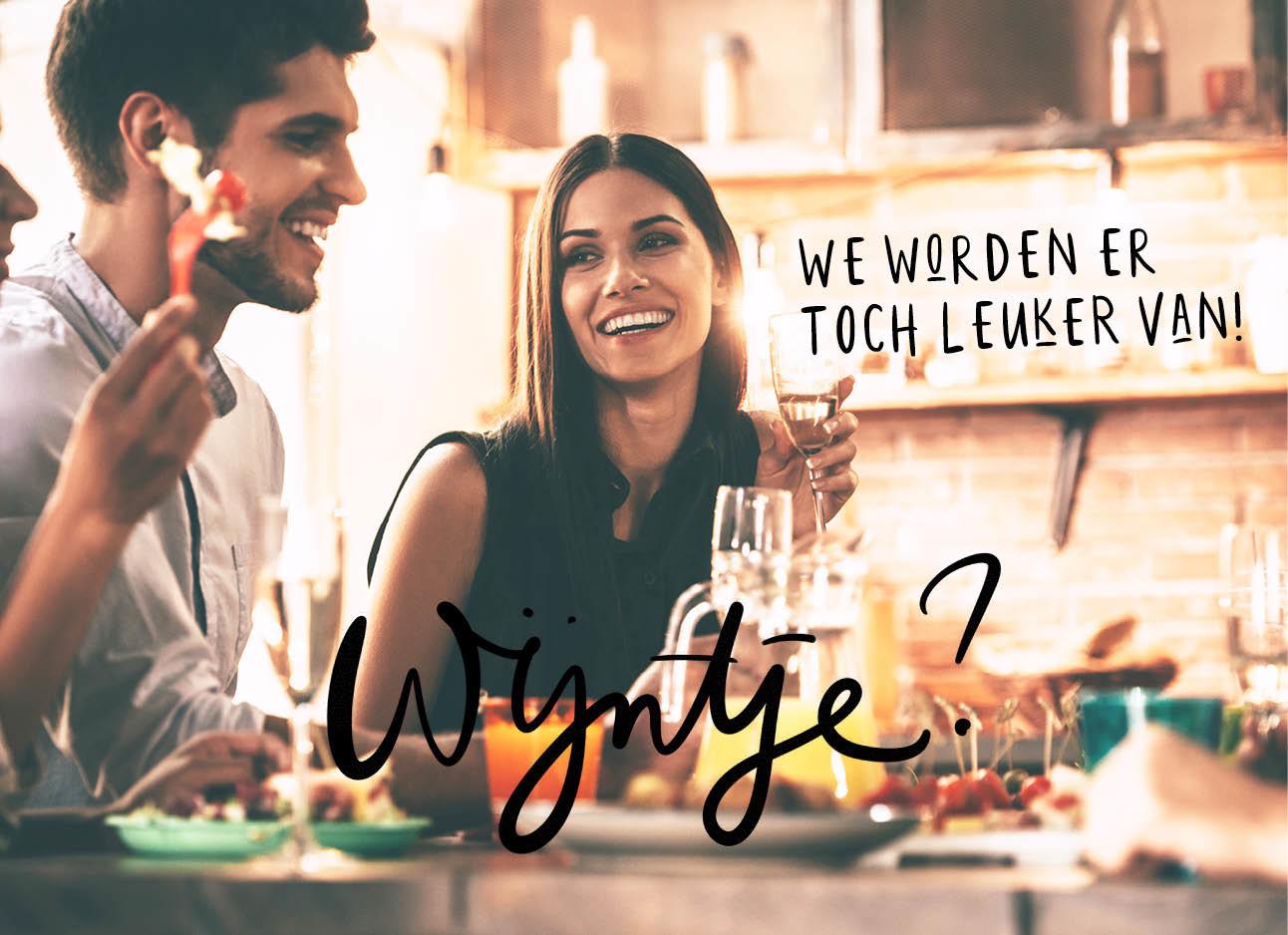 koppel drinkt wijn bij het diner en lacht