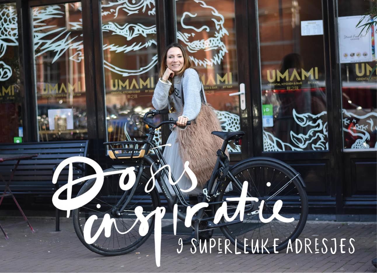 may lachend op de fiets door amsterdam in de straat de Overtoom met een rok en laarzen aan en een pluis tas