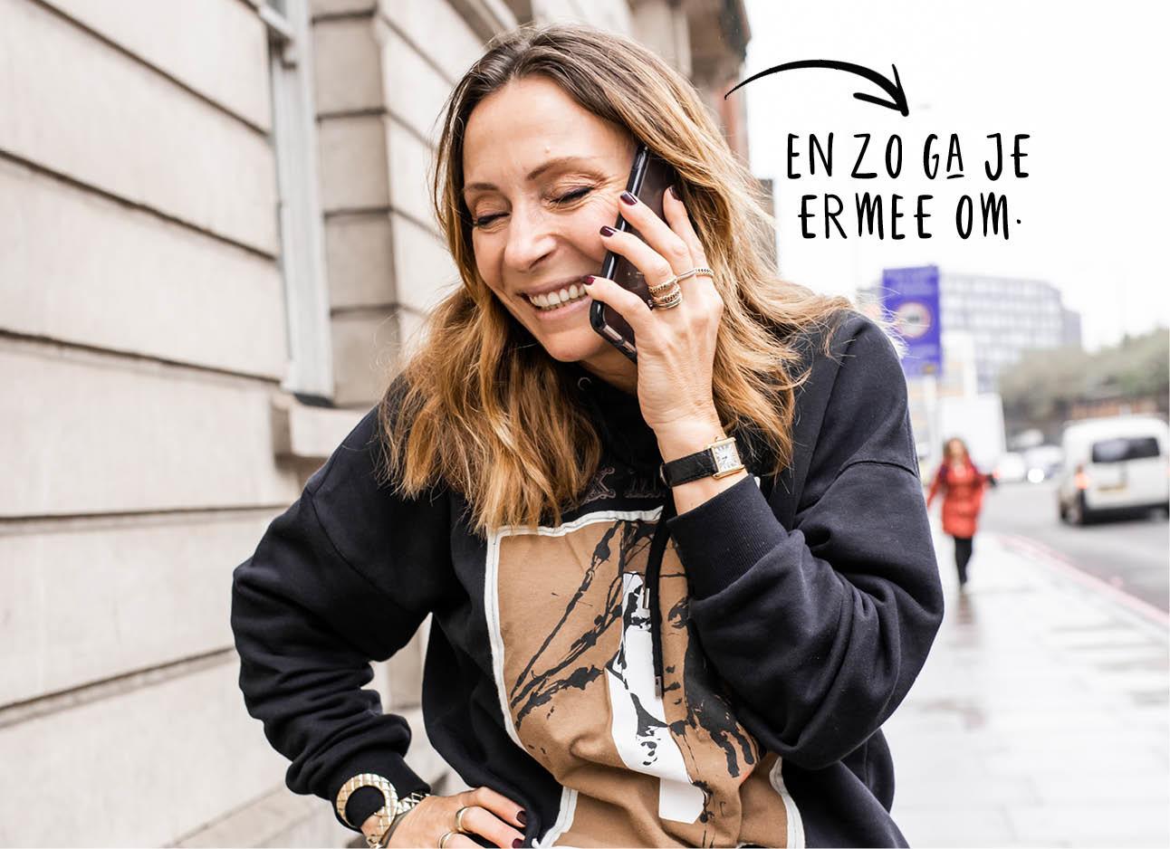 may-britt lachend aan de telefoon in London met een Max Mara thuis aan Iphone