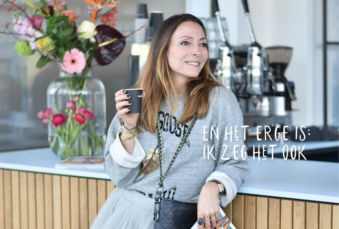 may lachend in de koffiesalon met haar chanel tas en koffie in haar handen