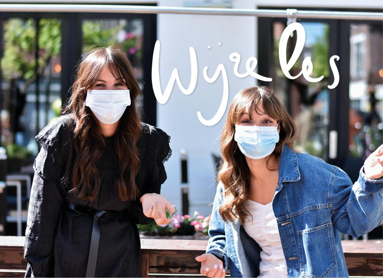 Lilian en Kiki lachend op straat met mondkapje