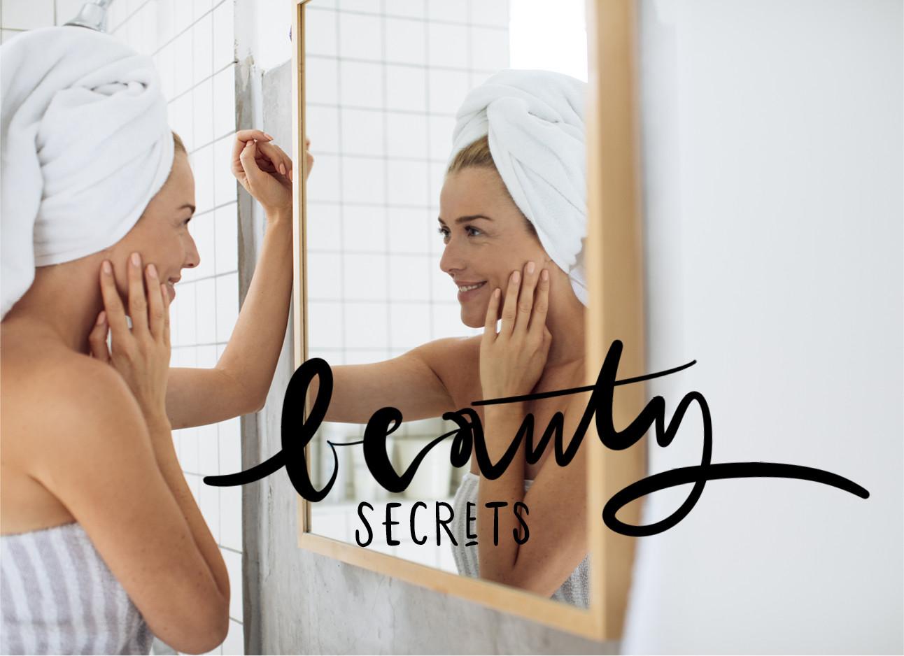 vrouw kijkend in de spiegel met handdoek op haar hoofd