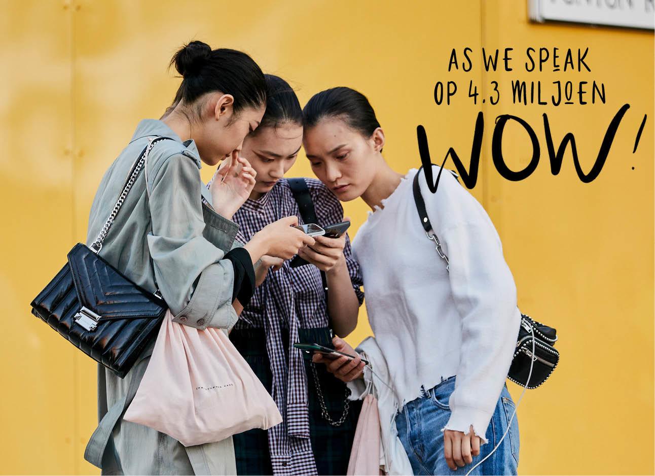Nieuwtje sussex, drie meiden kijken naar een telefoon, gele achtergrond