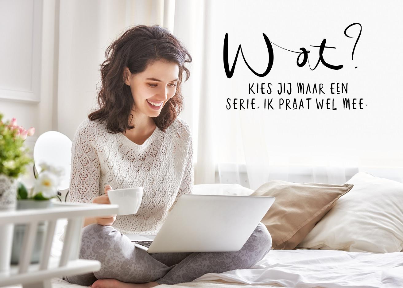 vrouw op bed met thee en kijkt lachend naar haar scherm