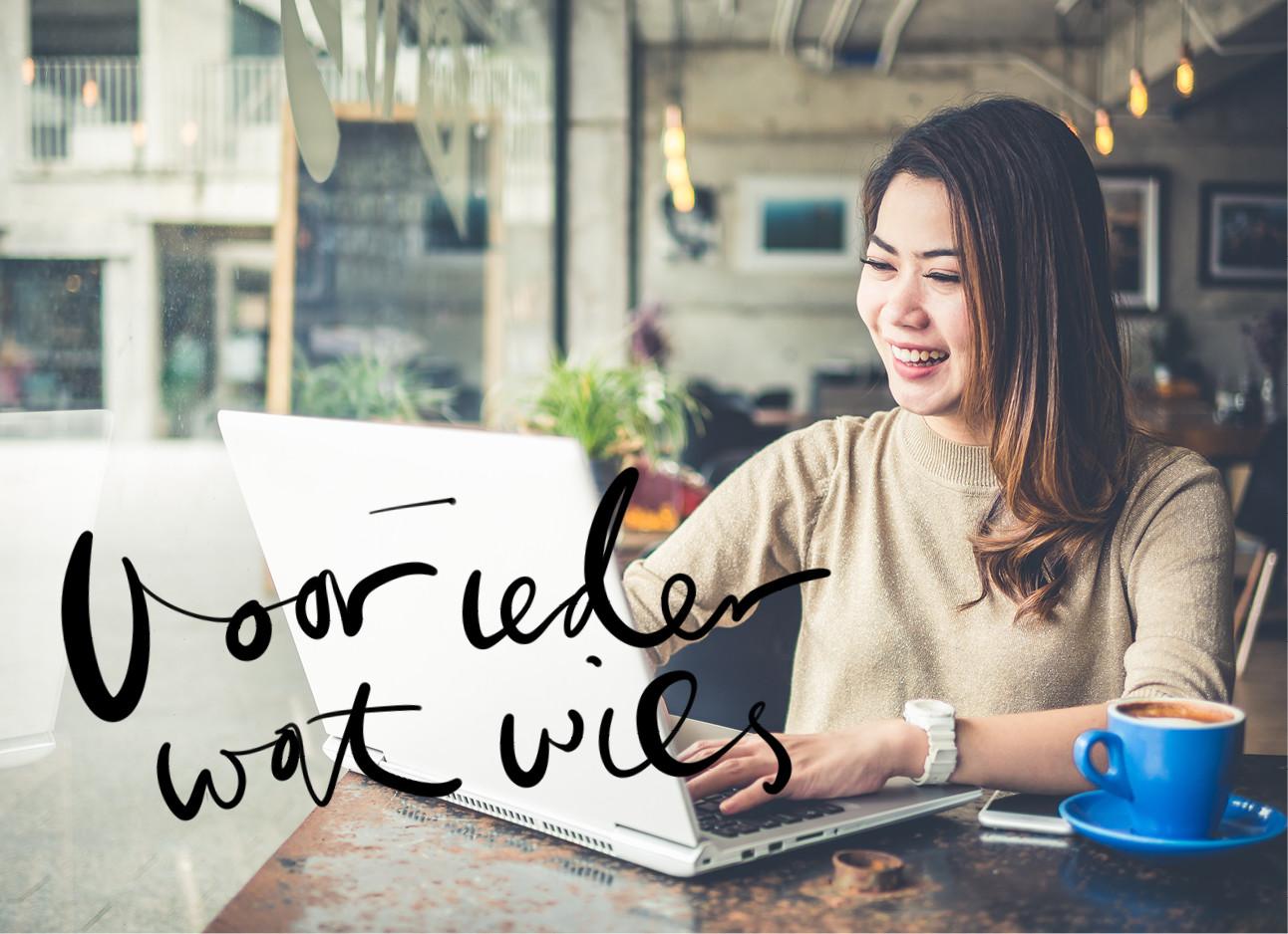 Een aziatisch meisje dat aan het werk is achter haar laptop en lacht