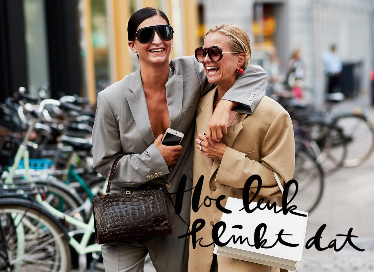 twee dames in een suit lachend over straat met telefoon in de hand, hoe leuk klinkt dat