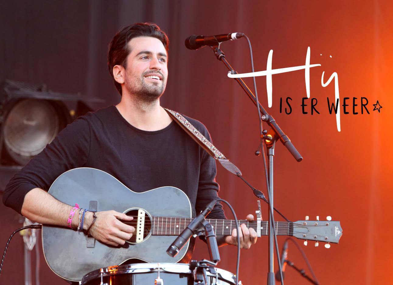 Dotan lachend op het podium met zijn gitaar