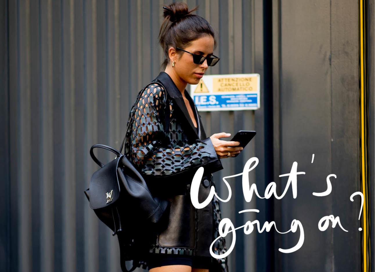 vrouw kijkt op haar telefoon in zwarte kleding
