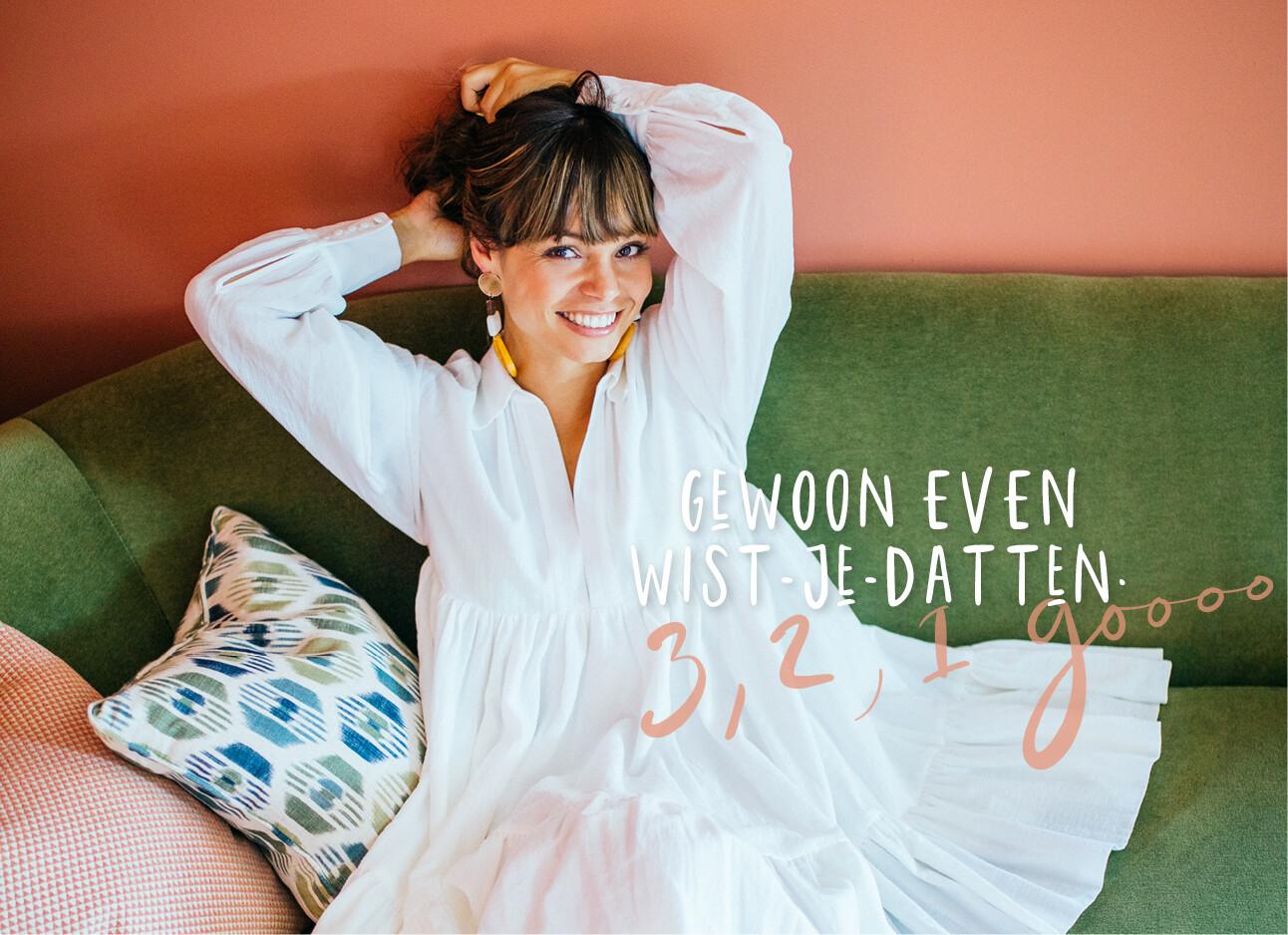 kiki lachend in een witte jurk op de bank