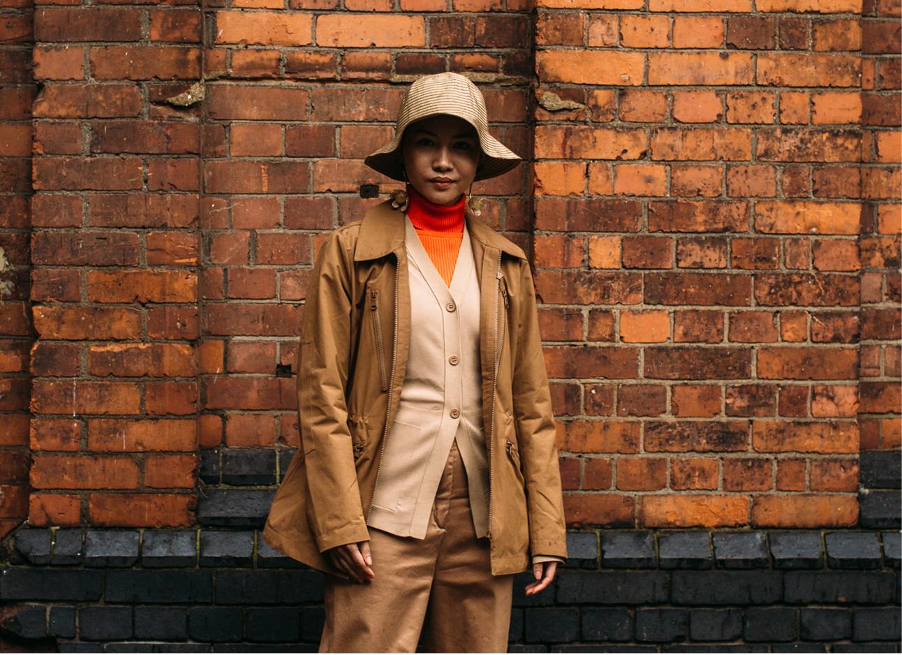 streetstyle beeld. Vrouw met een oranje coltrui aan, bruinen broek, jas, shirt en een buckethat op