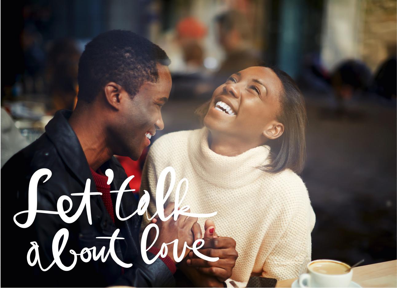 een koppel dat samen lachend in een cafe zitten