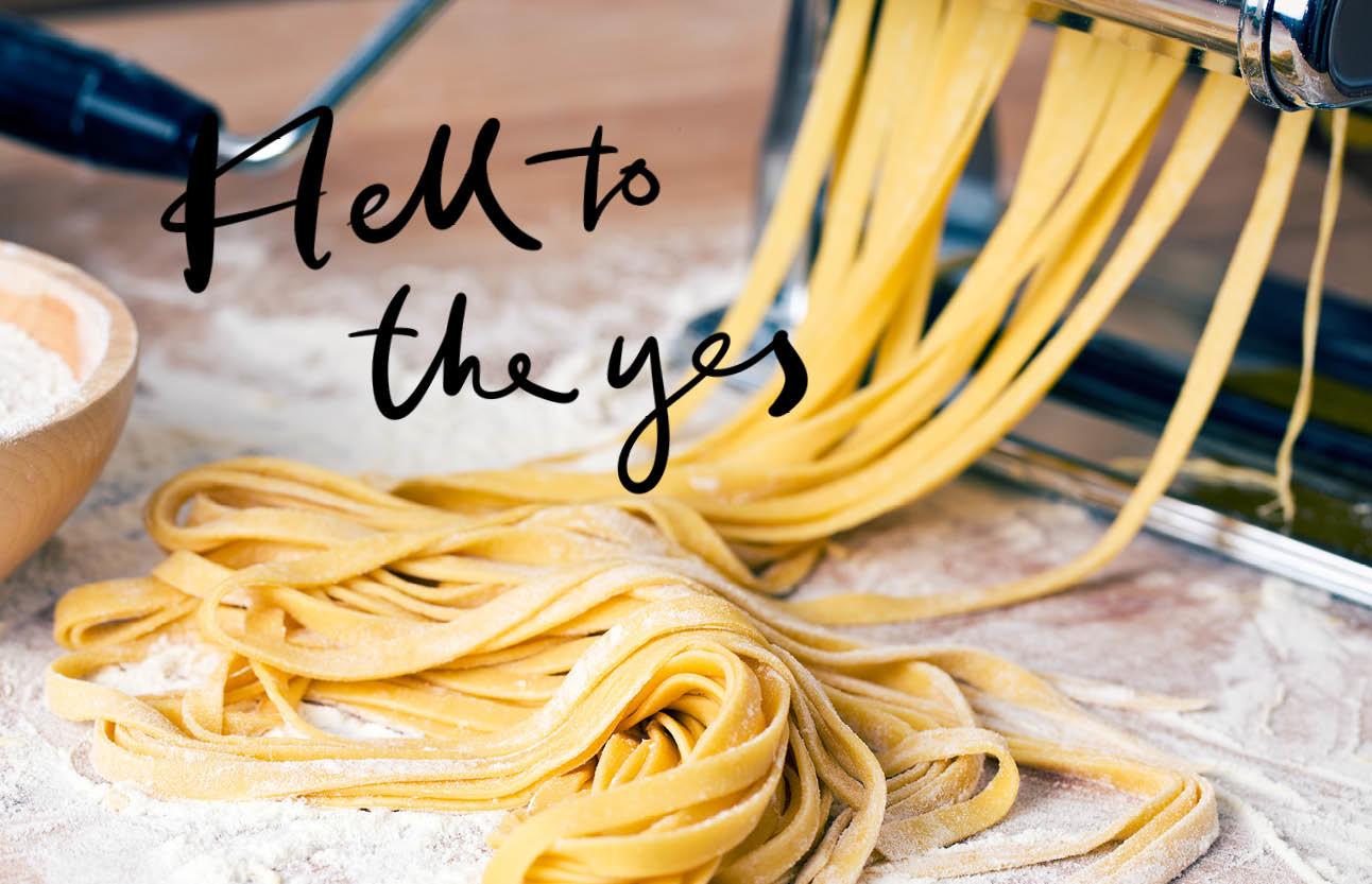 pasta rolt uit een pasta machine op een tafel met meel