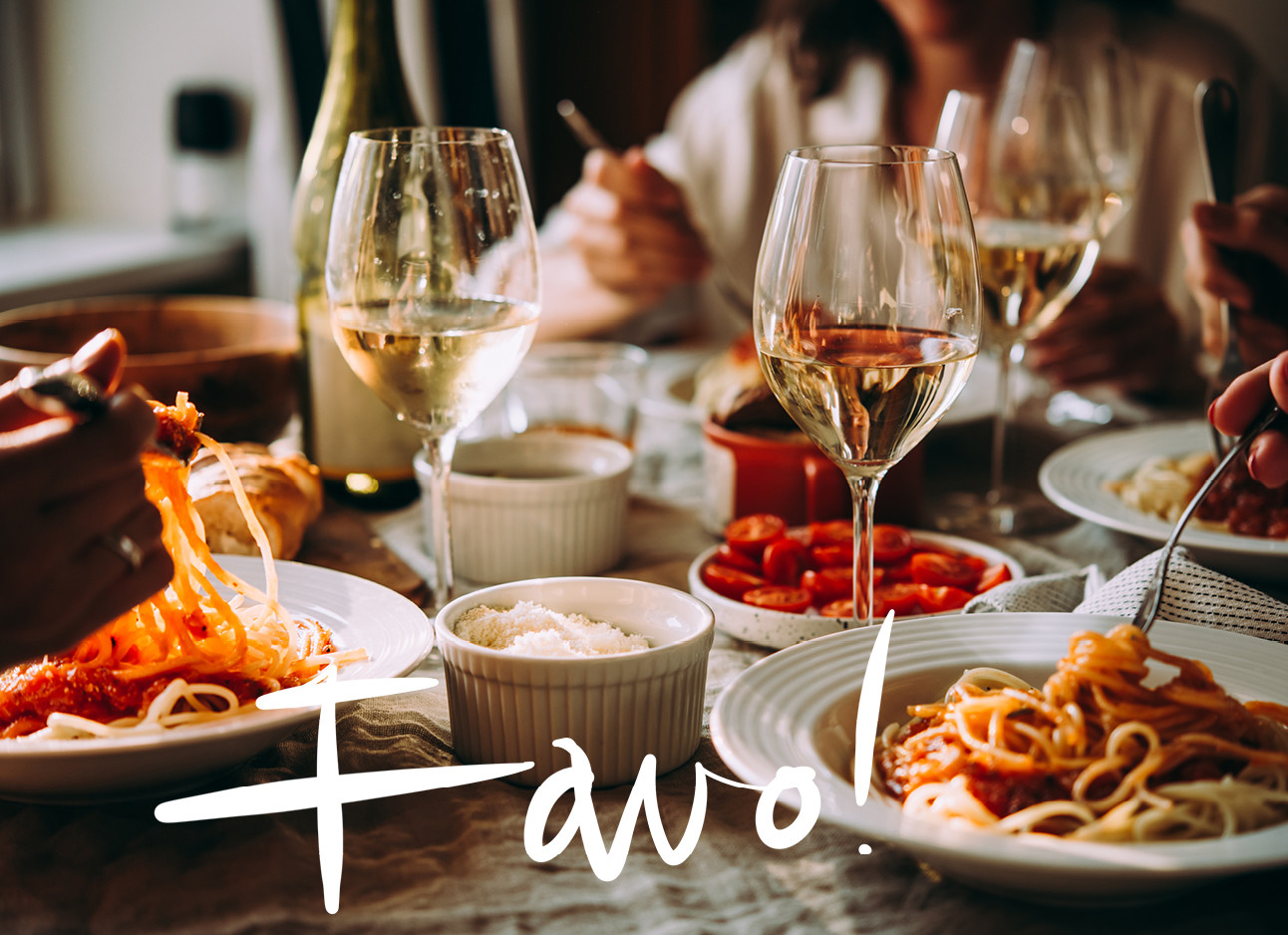 friends eating spaghetti together and drinking wine