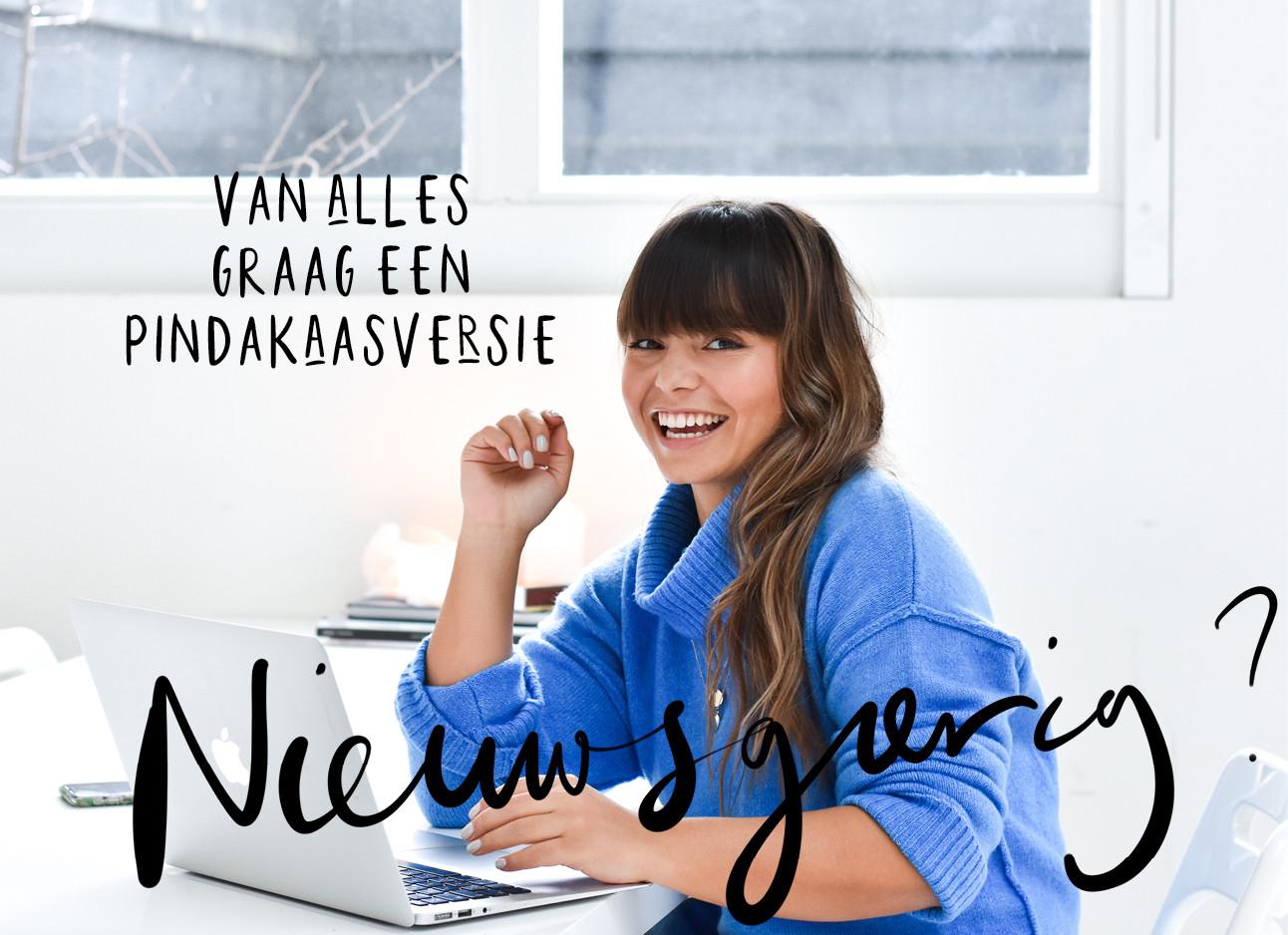 Kiki die lachend achter haar laptop zit en een blauwe trui draagt