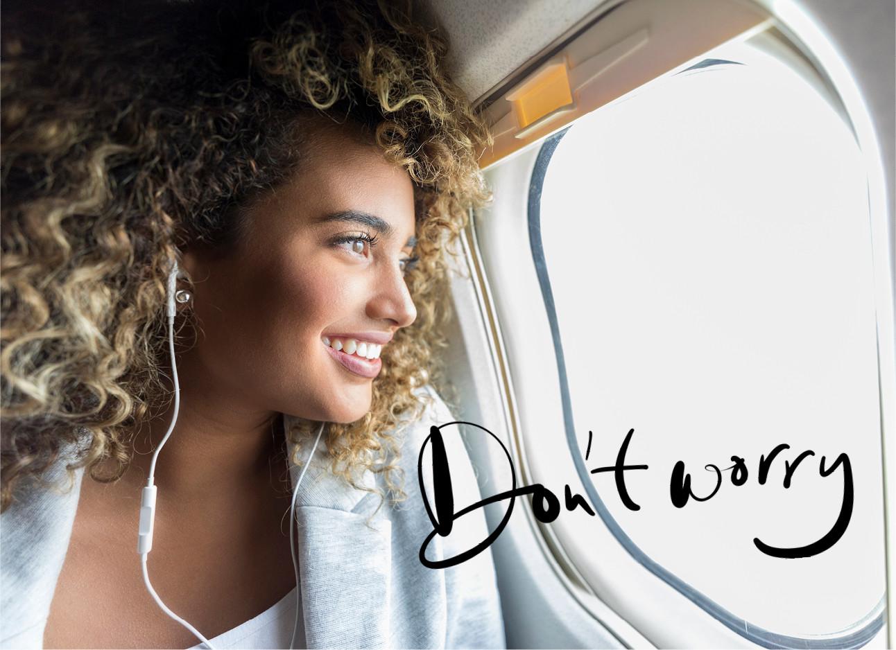 vrouw met krullen zit in het vliegtuig, kijkt lachend uit het raam en heeft oordopjes in
