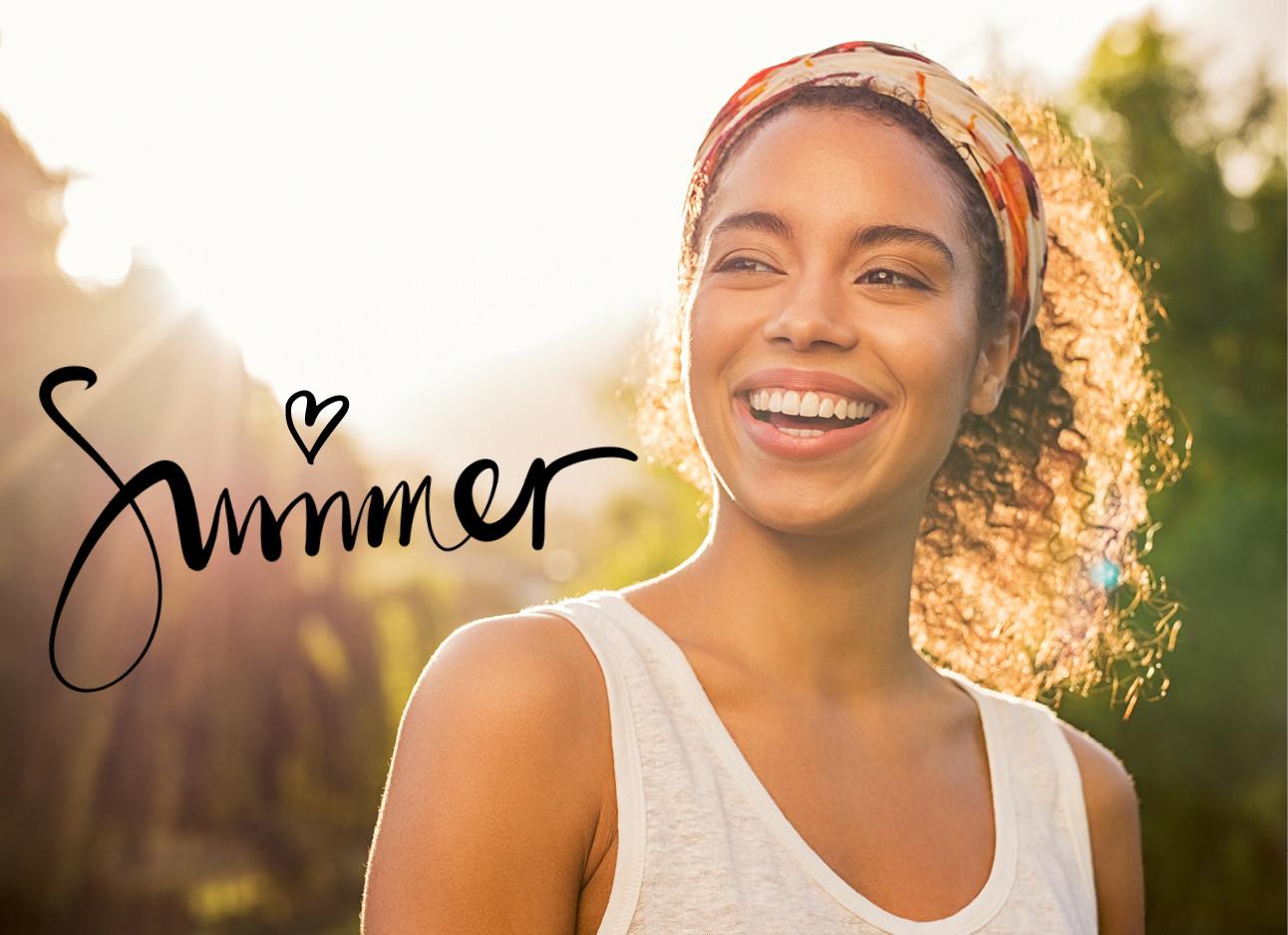 getinte vrouw met een haarband en krullen lachend, de zon, summer, hartje