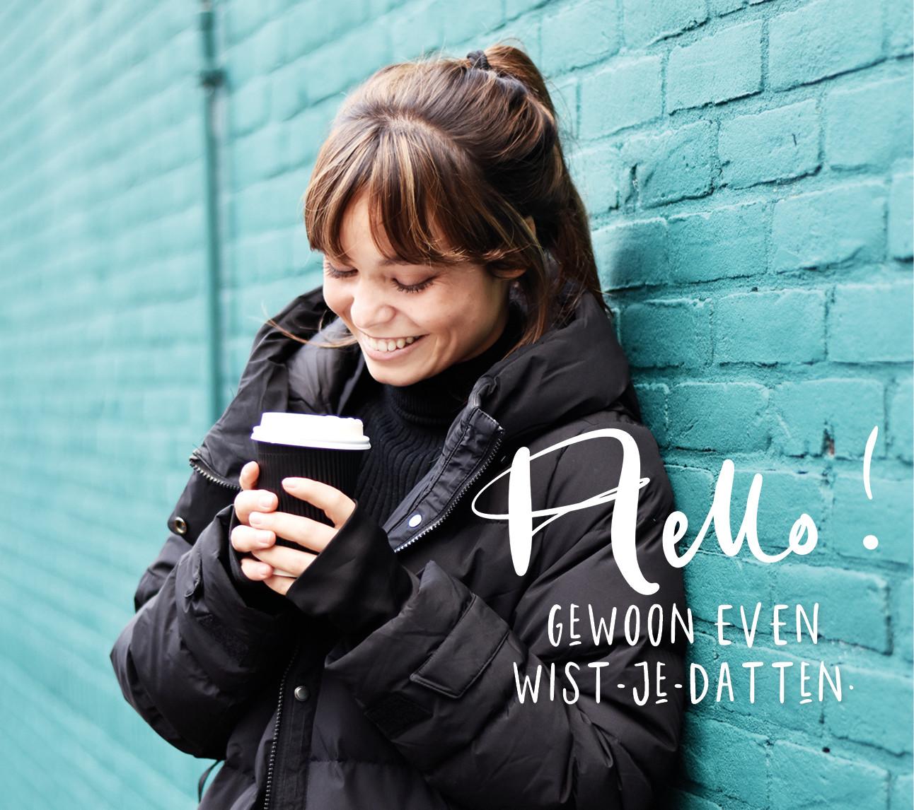 kiki lachend met beker koffie in haar handen buiten op straat