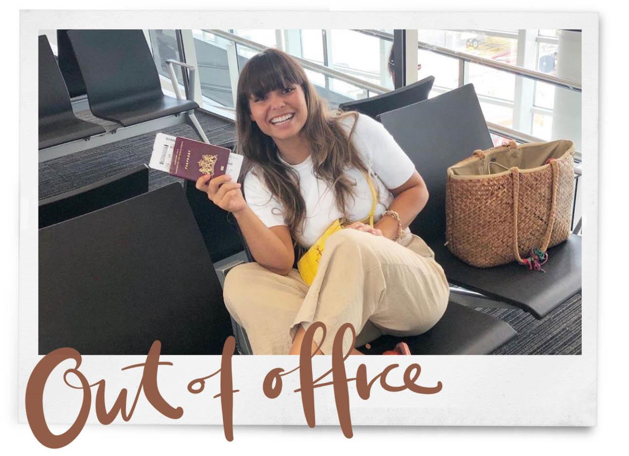 Kiki van duren op schiphol, beige broek en wit shirt draagt ze, naast haar staat een beige tas en ze houdt haar paspoort vast