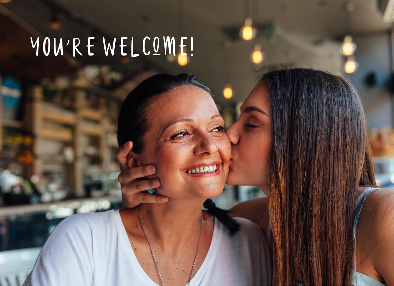 dochter geeft moeder een kus op de wang, de moeder lacht en draagt een wit t-shirt, foto is genomen in een restaurant youre welcome
