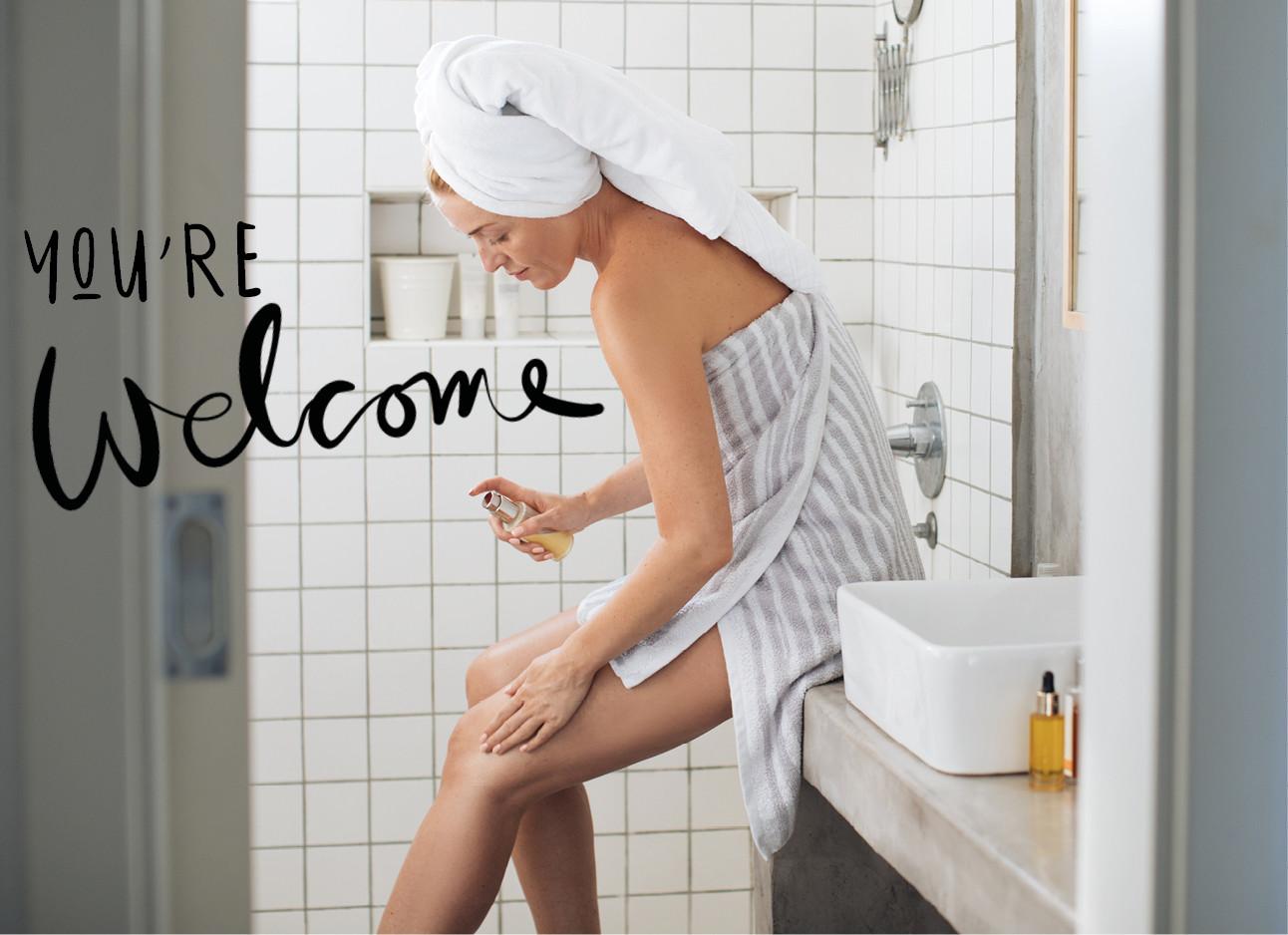 marion post over huidverzorging, een vrouw in de badkamer met een handdoek op haar hoofd en een om haar lichaam, smeert haar benen in met een creme, naast de wastafel staat een verzorgings olie