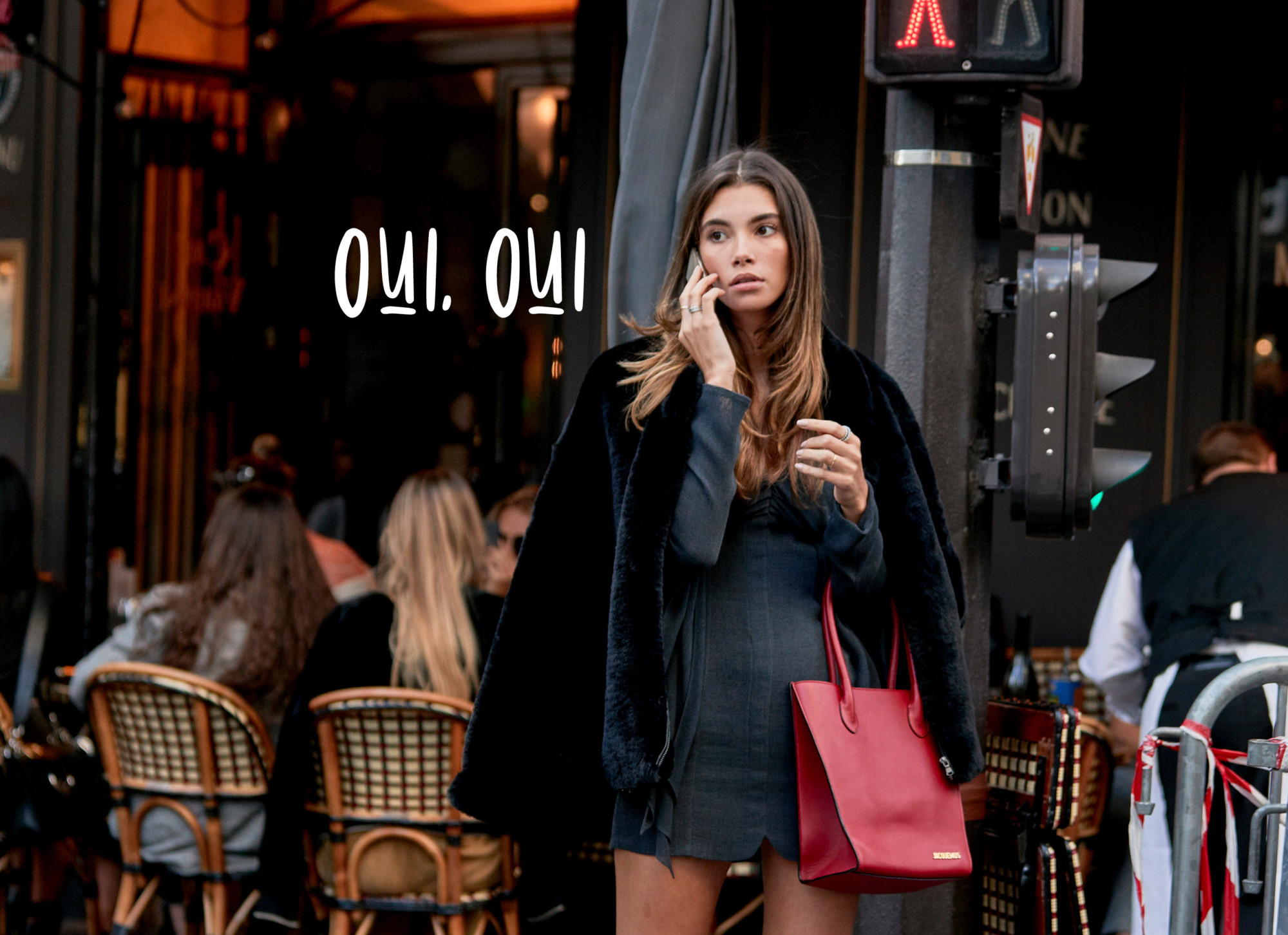 meisje aan de telefoon metrode tas en zwarte jas en blauw jurkje met blote benen in parijs voor een terras