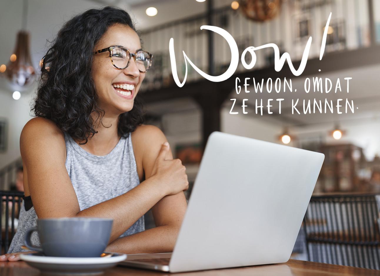 een meisje in een cafe dat lacht achter een laptop