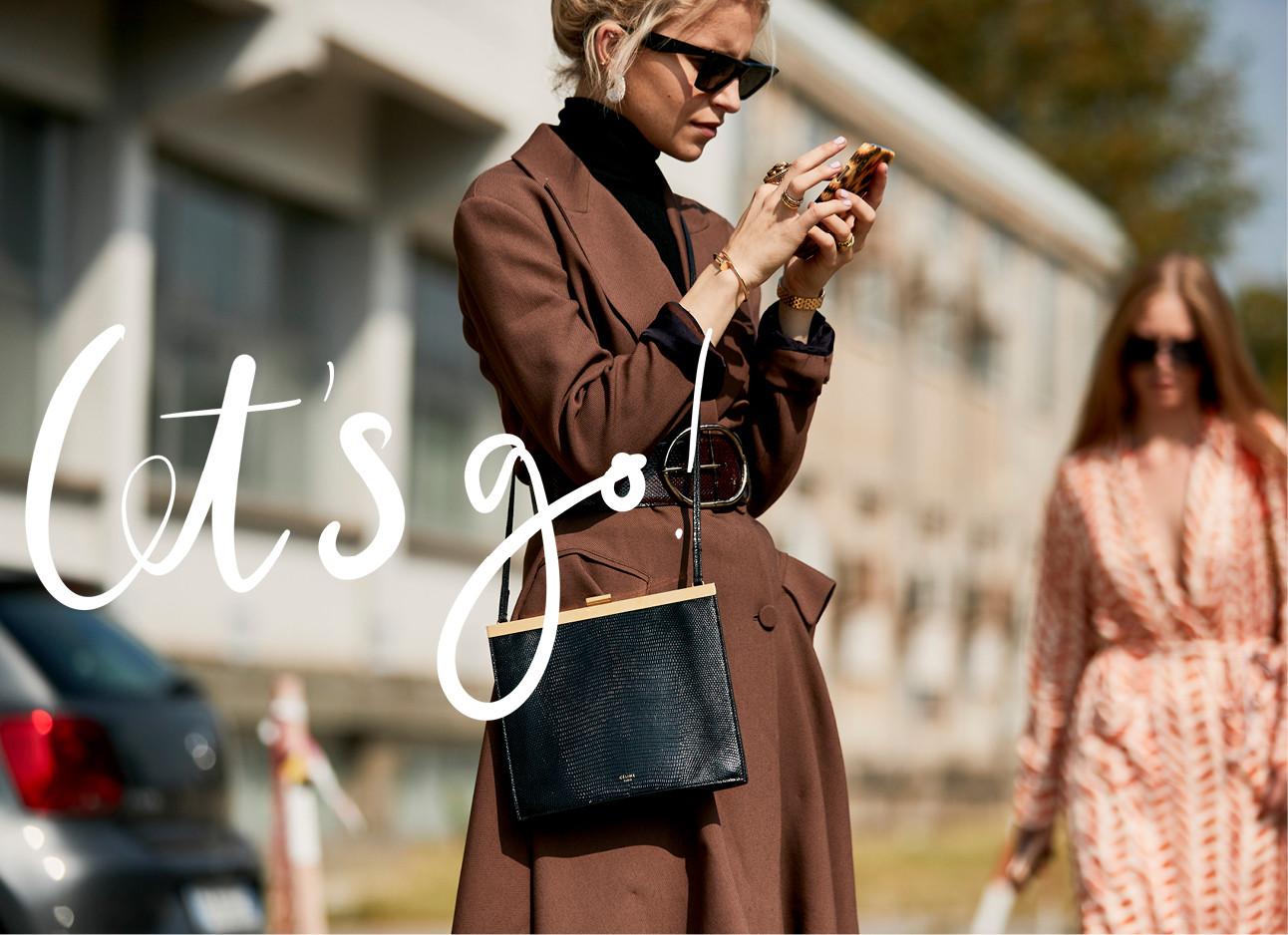 meisje op haar mobiel met bruine jas en zwarte tas