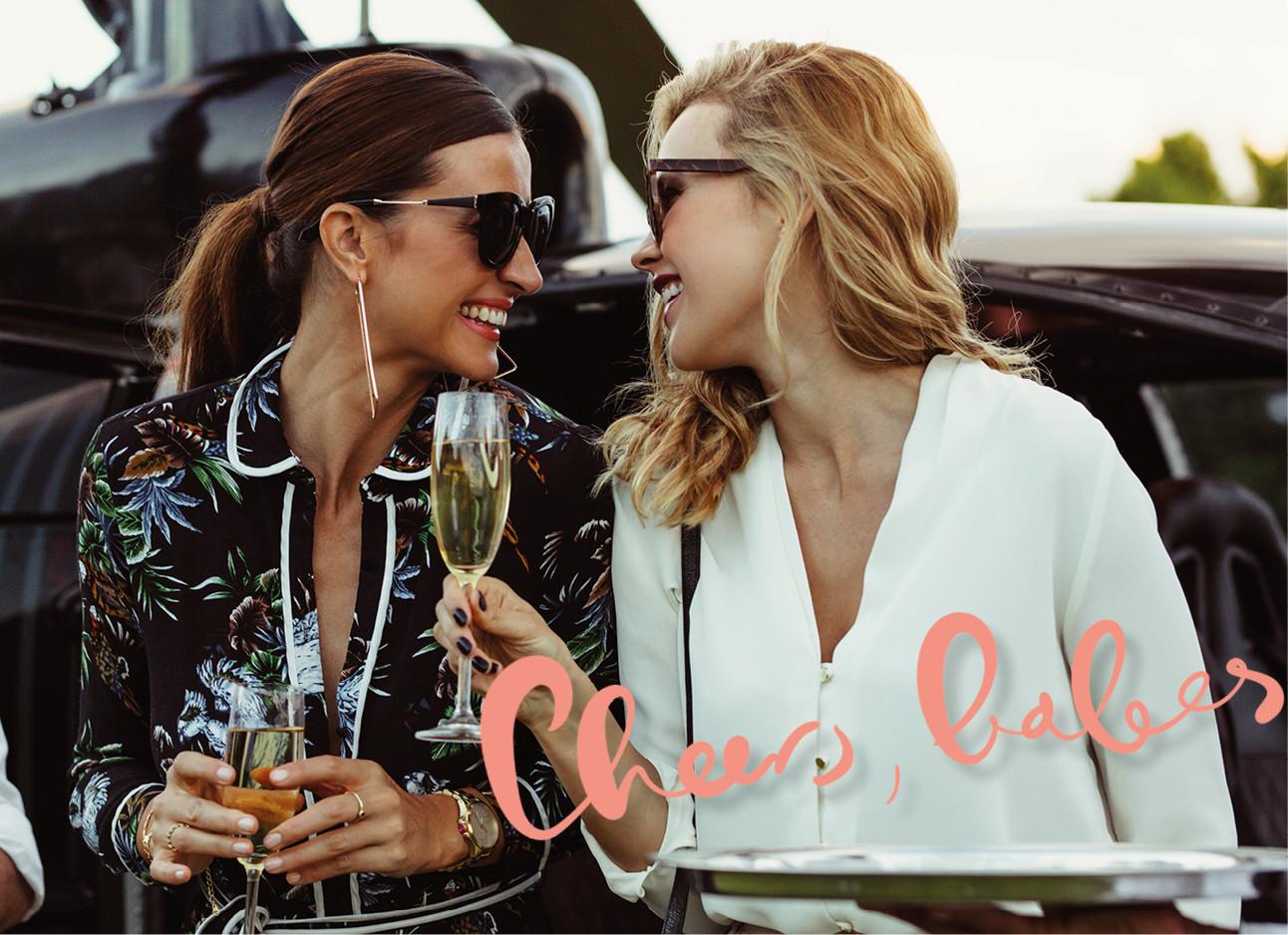 twee dames stappen uit een helikopter, ze dragen zonnebrillen, drinken champagne en lachen naar elkaar. cheers babes