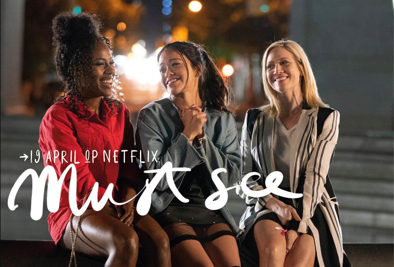 Drie vrouwen op een bankje buiten lachend