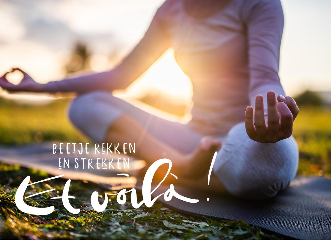 Een meisje dat Yoga aan het doen is op het gras bij een ondergaande zon