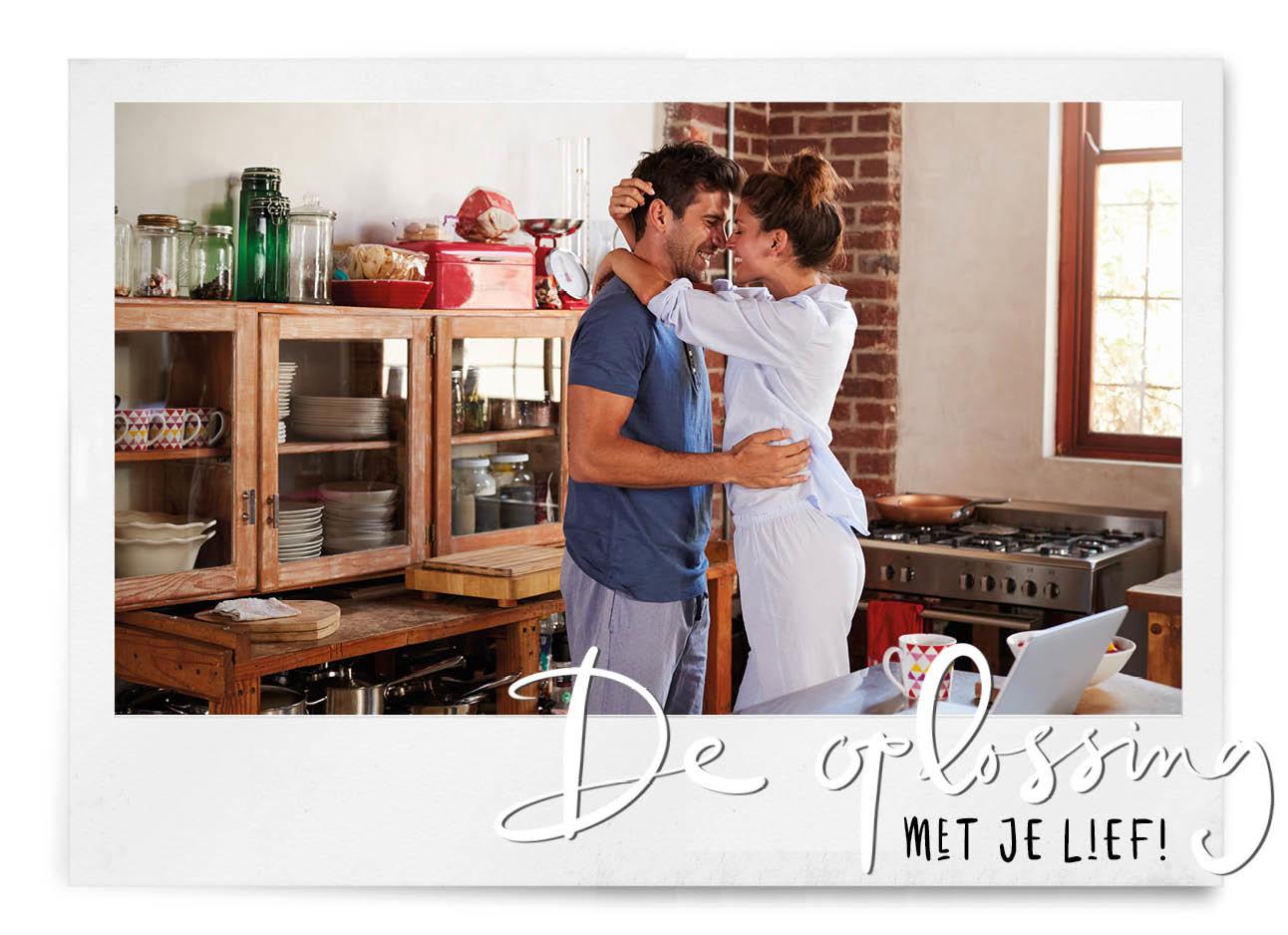 vrouw en man in de keuken in pyjama kussen lachend