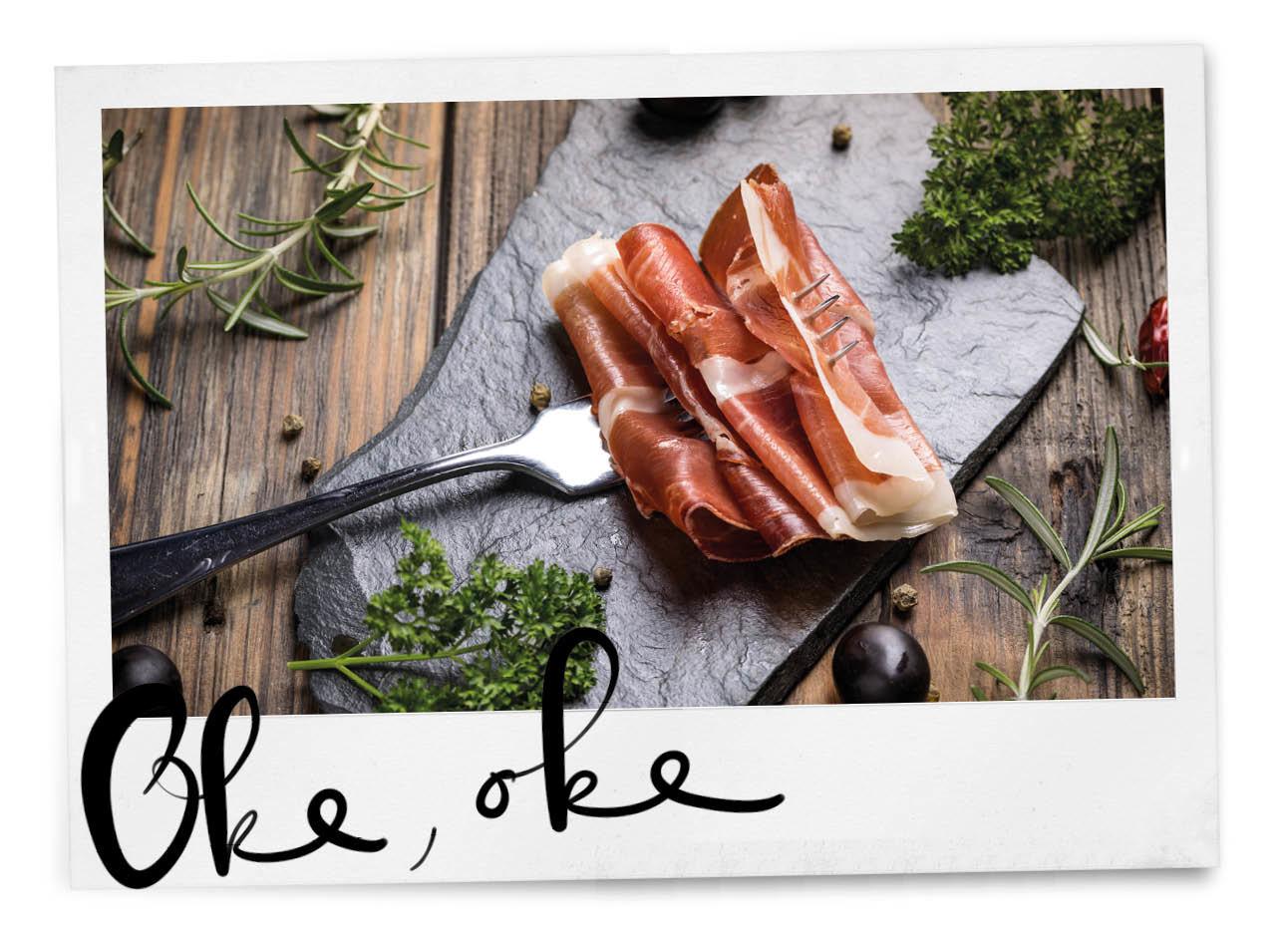 charcuterie op een snijplank met een vork en verse kruiden er omheen, iberico ham of serano ham