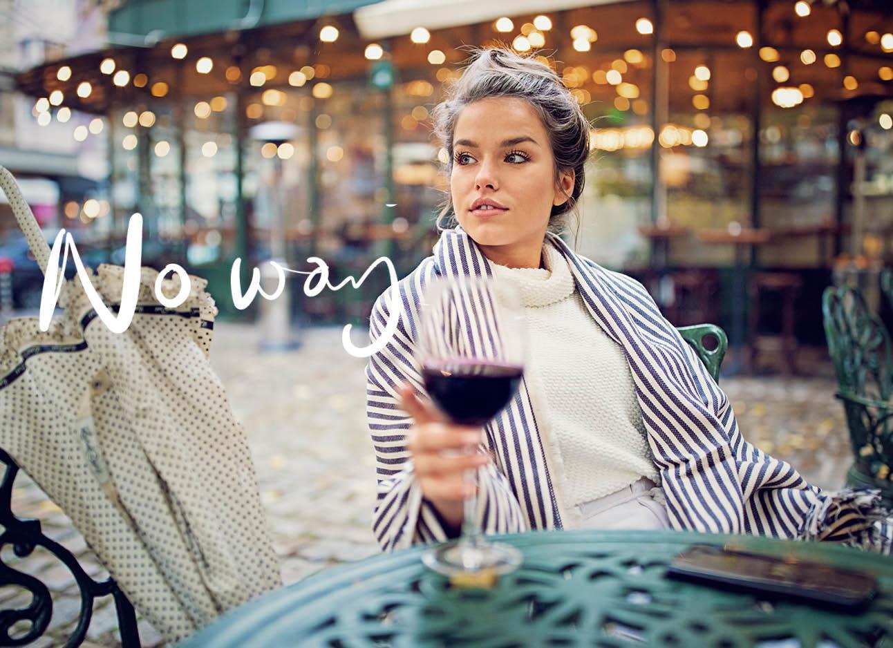 vrouw in streepjes colbert drinkt rode wijn